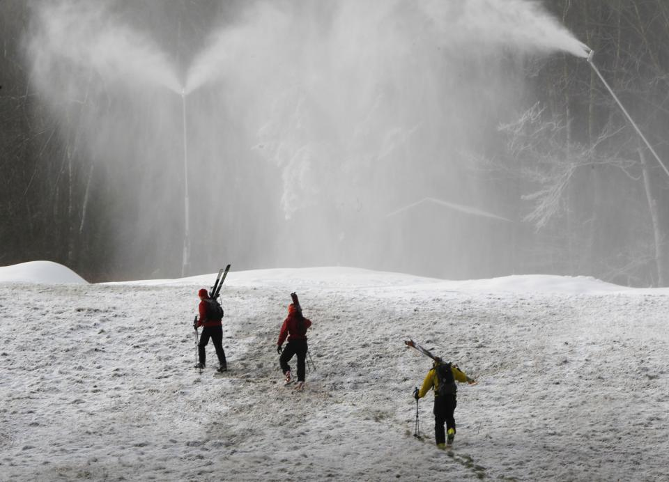 This Nov. 15, 2012 file photo shows skiers hiking up the mountain at the Stowe resort as snow guns make fresh snow in Stowe, VT. The ground might be bare, but ski areas across the Northeast are making big investments in high-efficiency snowmaking so they can open more terrain earlier and longer. (AP Photo/Toby Talbot)