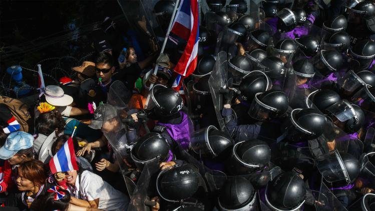 Anti-government protesters clash with riot police during mass rally outside house of PM Yingluck in Bangkok
