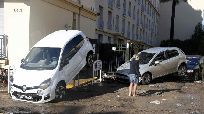 A woman stands barefoot in the mud as she look at cars which were damaged after flooding caused by torrential rain in Cannes