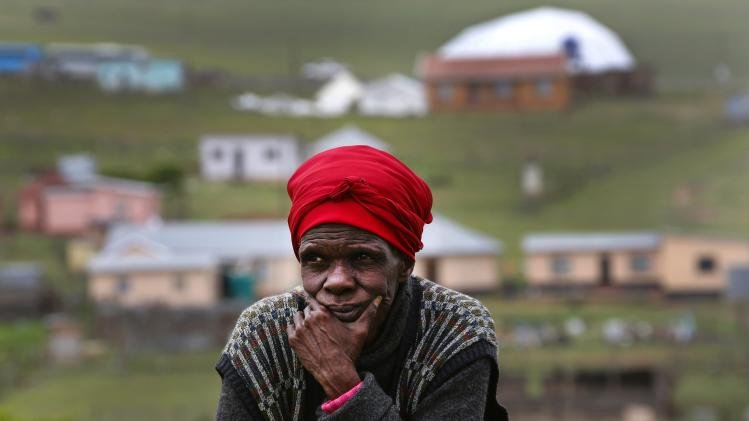 A woman sits at her garden at the perimeter of former South African President Mandela's property in Qunu
