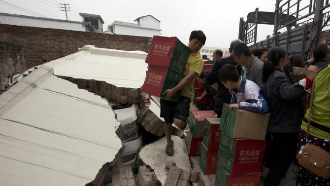 A man carrying boxes of water walks on the remains of a wall that had collapsed onto a vehicle after an earthquake struck the county seat of Lushan in southwestern China's Sichuan province, Monday, April 22, 2013. Saturday's earthquake in Sichuan province killed at least 186 people, injured more than 11,000 and left nearly two dozen missing, mostly in the rural communities around Ya'an city, along the same seismic fault where a devastating quake to the north killed more than 90,000 people in Sichuan and neighboring areas five years ago in one of China's worst natural disasters. (AP Photo/Ng Han Guan)