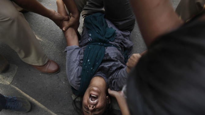An Indian protestor shouts slogans as police removes her from outside prime minister's residence during a protest against the rape of a 5-year-old girl in New Delhi, India, Sunday, April 21, 2013. The girl was allegedly kidnapped, raped and tortured by a man and then left alone in a locked room in India's capital for two days. (AP Photo/Manish Swarup)
