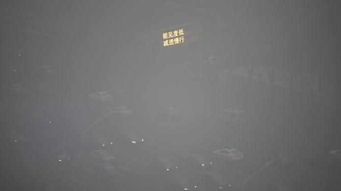 Vehicles pass on a road as smog covers China's capital Beijing