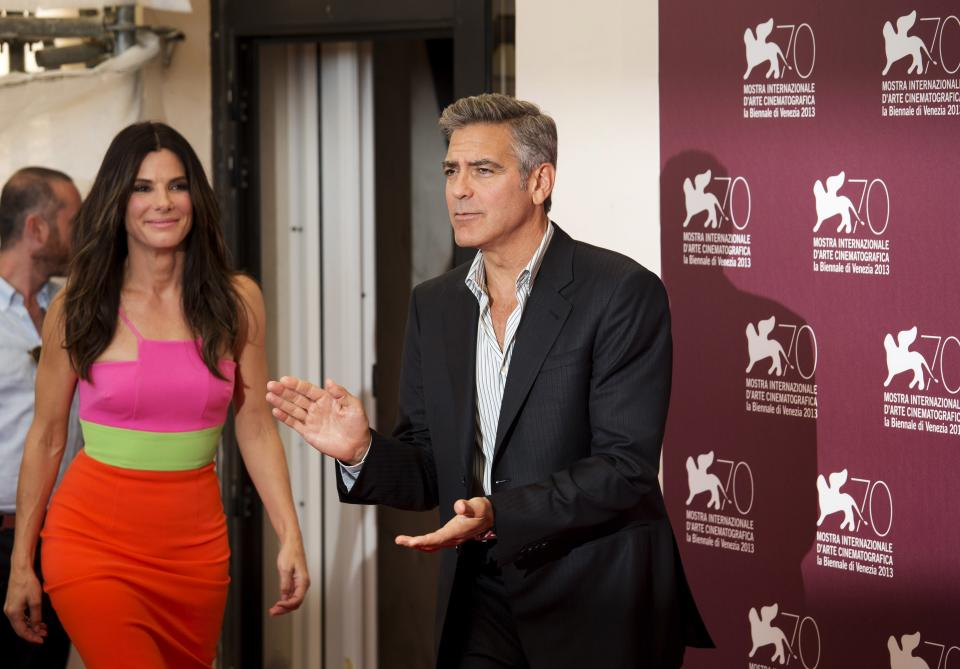 Actor George Clooney, right, gestures to photographers as he arrives with Sandra Bullock, left, to promote their film Gravity during a photo call at the 70th edition of the Venice Film Festival held from Aug. 28 through Sept. 7, in Venice, Italy, Wednesday, Aug. 28, 2013. (AP Photo/David Azia)