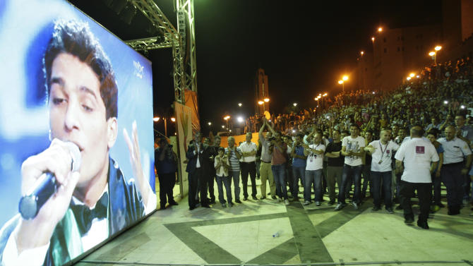 """Palestinians watch the performance of Palestinian singer Mohammed Assaf, a contestant in a regional TV singing contest, on a large screen in the West Bank city of Nablus, Saturday, June 21, 2013. Palestinians relished a rare moment of pride and national unity Saturday after a 23-year-old wedding singer from a refugee camp in the Gaza Strip won """"Arab Idol,"""" a regional TV singing contest watched by millions of people. (AP Photo/Nasser Ishtayeh)"""