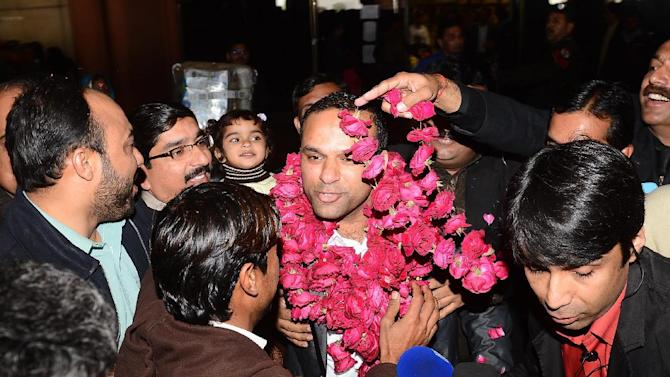 """In this picture taken on Thursday, Dec. 27, 2012, Pakistani fans receive Muhammad Shahid Nazir, center, who sings """"One Pound Fish,"""" upon his arrival from London at Lahore airport in Pakistan. The 31-year-old Pakistani fishmonger catapulted to fame in recent weeks in the unlikeliest of circumstances: while hawking frozen snapper and mackerel for one British pound ($1.61) at Queens Market in London. """"One Pound Fish changed my whole life,"""" said Nazir, who returned to Pakistan to a hero's welcome and has been inundated with requests to perform and do advertisements. """"I am so happy now.""""(AP Photo/Hamza Ali)"""