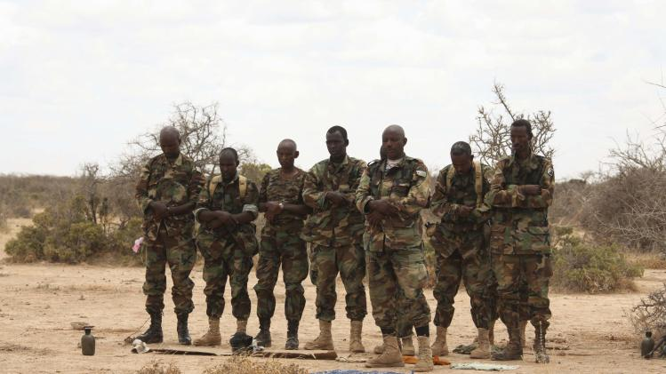 AMISOM soldiers, belonging to Djiboutian contingent of AU mission, pray before embarking on operation to capture al Shabaab-held town of Buule Burde