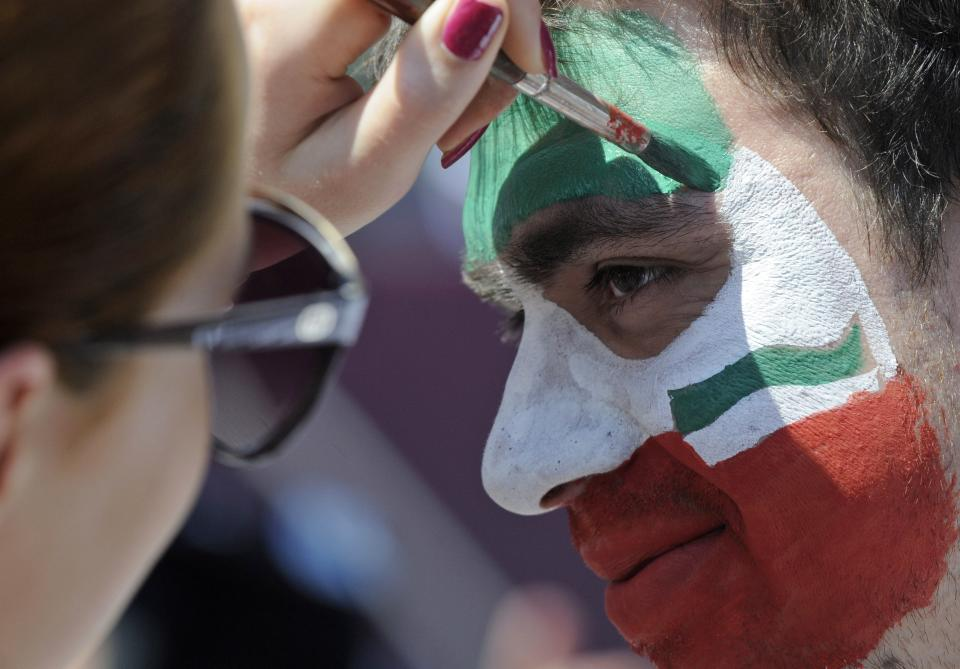 An Italian soccer fan has his face painted  ahead of the Euro 2012 soccer championship final match between  Spain and Italy in the fan zone in Kiev, Ukraine, Sunday, July 1, 2012. (AP Photo/Sergei Chuzavkov)