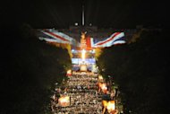 A beacon (C) is lit by Queen Elizabeth II amid a fireworks display outside Buckingham Palace, on June 4, 2012, to mark the end of the Diamond Jubilee Concert