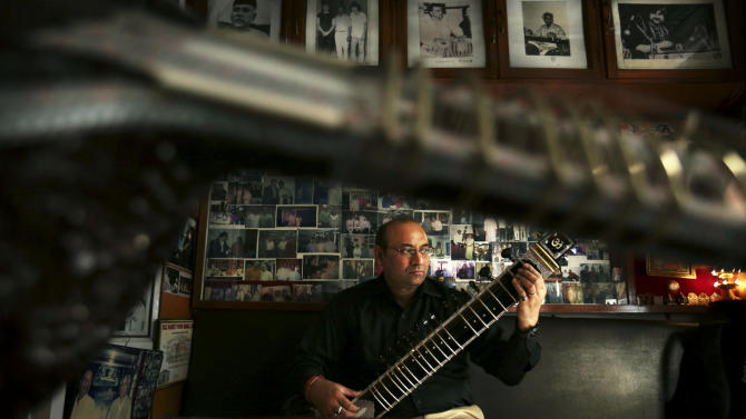 """Indian traditional instrument craftsman Sanjay Sharma plays a sitar at his store Riki Ram's Music in New Delhi, India, Thursday, Dec. 13, 2012. For close to a 100 years Sharma's family has created musical instruments for legendary Indian musicians. But none more famous than sitar virtuoso Ravi Shankar who died Tuesday at age 92. Described as """"the godfather of world music"""" by Beatle George Harrison, Shankar introduced millions of Westerners to the sitar and the centuries-old traditions of Indian classical music.(AP Photo/Kevin Frayer)"""