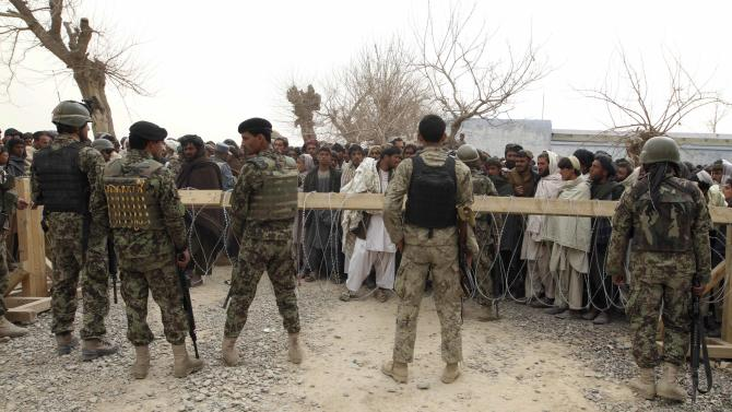 In this Sunday, March 11, 2012 photo, Afghan Army soldiers stand guard as a crowd gathers outside a military base in Panjwai, Kandahar province south of Kabul, Afghanistan. An Afghan youth recounted on Monday the terrifying scene in his home as a lone U.S. soldier moved stealthily through it during a killing spree, then crouched down and shot his father in the thigh as he stepped out of the bedroom. The soldier, now in U.S. custody, is accused of killing 16 Afghan civilians in their homes in the middle of the night between Saturday and Sunday and then burning some of their corpses. Afghan President Hamid Karzai said nine of those killed were children and three were women.(AP Photo/Allauddin Khan)