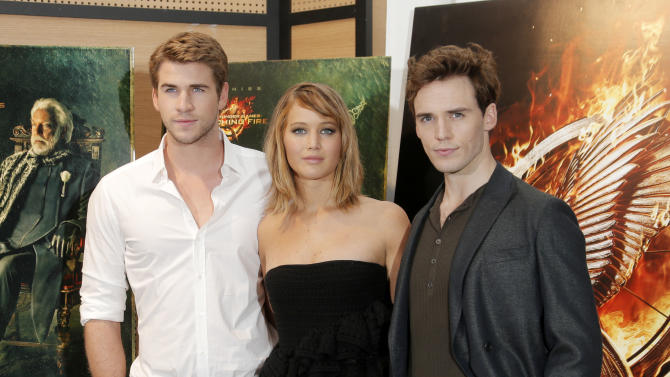 From left, actors Liam Hemsworth, Jennifer Lawrence and Sam Claflin pose for photographers during a photo call for the film The Hunger Game: Catching Fire at the 66th international film festival, in Cannes, southern France, Saturday, May 18, 2013. (Photo by Todd Williamson/Invision/AP)
