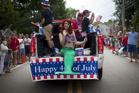A girl dressed as a mermaid rides on the back of a pickup truck through Barnstable Village on Cape Cod, during the annual Fourth of July Parade celebrating the country's Independence Day, in Barnstable, Massachusetts