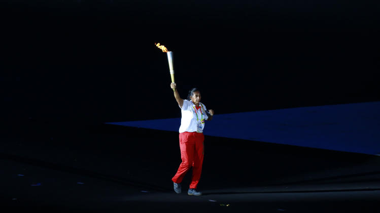 Former athlete Tin Lay of Myanmar runs with the torch during the opening ceremony of the 27th Southeast Asian (SEA) Games in Naypyitaw