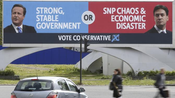 People walk under a conservative advertising hoarding, featuring David Cameron and Labour party leader, Ed Miliband, on a major road junction near to central London