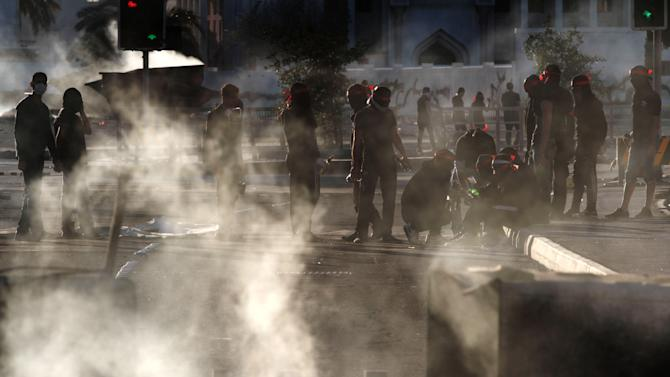 Bahraini anti-government protesters prepare for clashes with riot police during the second anniversary of the start a pro-democracy uprising in Sanabis, Bahrain, Thursday, Feb. 14, 2013. Security forces in Bahrain clashed on Thursday with anti-government protesters in street battles that left at least one boy dead amid high tensions on the second anniversary of the uprising in the Gulf nation, activists said. (AP Photo/Hasan Jamali)