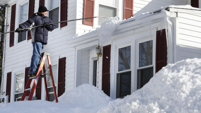 Luis Florian rakes snow off the roof of his home in Windsor, Conn., Sunday, Feb. 10, 2013.  A howling storm across the Northeast left much of the New York-to-Boston corridor covered with more than three feet of snow on Friday into Saturday morning.  Florian says he wants to clear the snow off the roof before the next storm. (AP Photo/Jessica Hill)