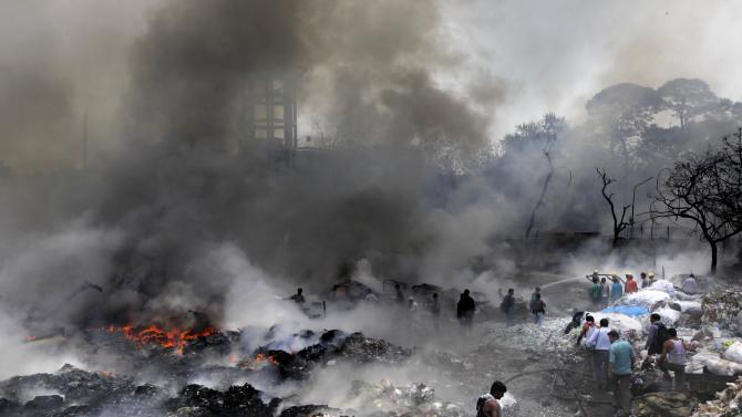 Residents and fire fighters try to douse down the fire at a scrap yard in New Delhi, India, Friday, June 22, 2012. The fire broke out in a scrap yard and adjoining shanty town behind a government hospital in central Delhi Friday morning, fire brigade officials said, the cause of the fire was not known. (AP Photo/Manish Swarup)