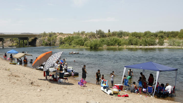 Families line the Salt River on Saturday, June 29, 2013, in Phoenix. Excessive heat warnings will continue for much of the Desert Southwest as building high pressure triggers major warming in eastern California, Nevada, and Arizona. Temperature's are expected to get as high as 118 degrees. (AP Photo/Rick Scuteri)