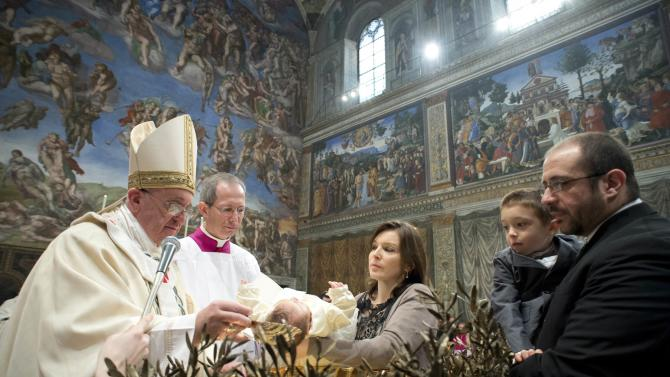 Pope Francis baptises one of 32 babies during a mass in the Sistine Chapel at the Vatican
