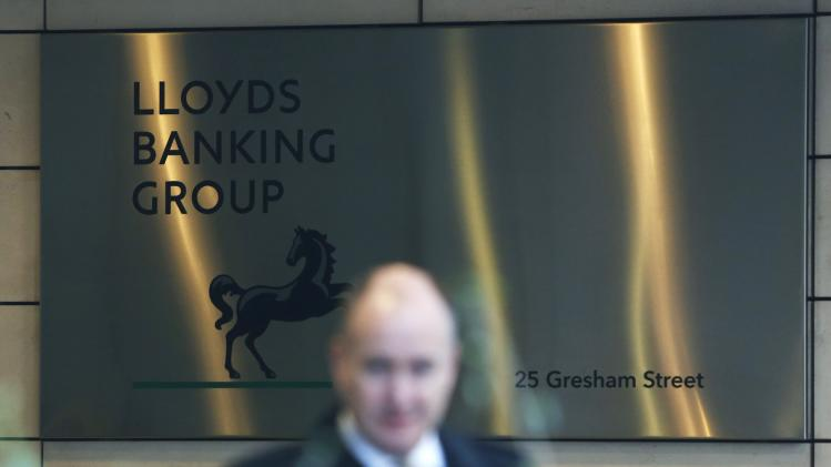 A man walks past the entrance to the head office of Lloyds Banking Group in the City of London