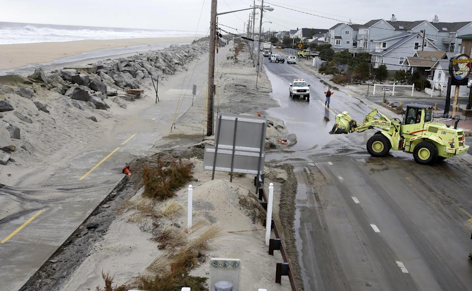 Crews clear a flooded road Thursday, March 7, 2013, in Sea Bright, N.J., after an overnight storm caused the ocean to breach a temporary dune. The lingering late-winter storm brought new damage Thursday to parts of the Jersey shore still struggling to recover from Superstorm Sandy. (AP Photo/Mel Evans)