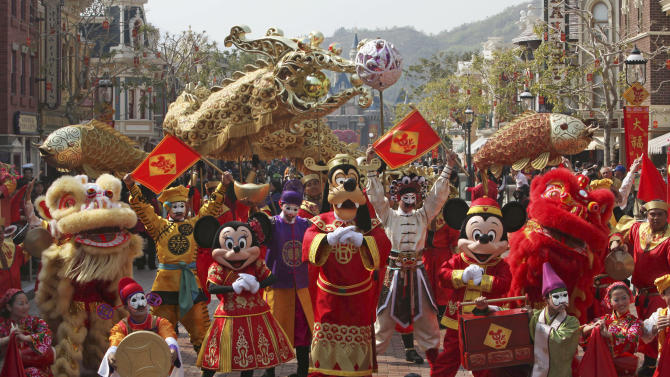 FILE - In this Jan. 15, 2008 file photo, Mickey mouse and other cartoon characters pose during a parade as celebrating the Chinese New Year with the year of the Ox in  Hong Kong Disneyland. Disneyland in the southern Chinese city of Hong Kong has turned a profit for the first time since it opened in 2005. The park said Monday, Feb. 18, 2013, it earned 109 million Hong Kong dollars ($14 million) in 2012.  (AP Photo/Kin Cheung, File)