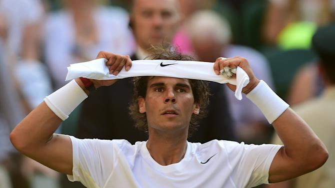 Spain's Rafael Nadal adjusts his headband between sets during the Wimbledon Championships on July 1, 2014