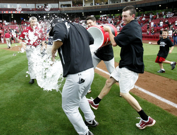 South Carolina pitcher Michael Roth and team manager Carter Scheetz, right, douse coach Ray Tanner after winning their NCAA college baseball tournament super regional game against Oklahoma in Columbia, S.C., Monday, June 11, 2012. (AP Photo/Mary Ann Chastain)