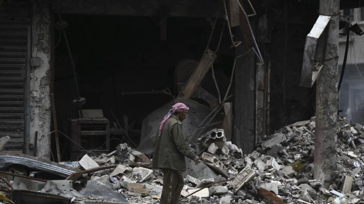 A man walks past buildings damaged by what activists said was shelling by forces loyal to President al-Assad in Deir al-Zor