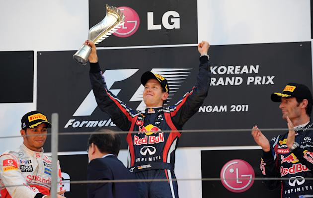 Red Bull-Renault driver Sebastian Vettel (C) of Germany celebrates his victory in the Formula One Korean Grand Prix on the podium along woth second placed McLaren-Mercedes driver Lewis Hamilton of Bri