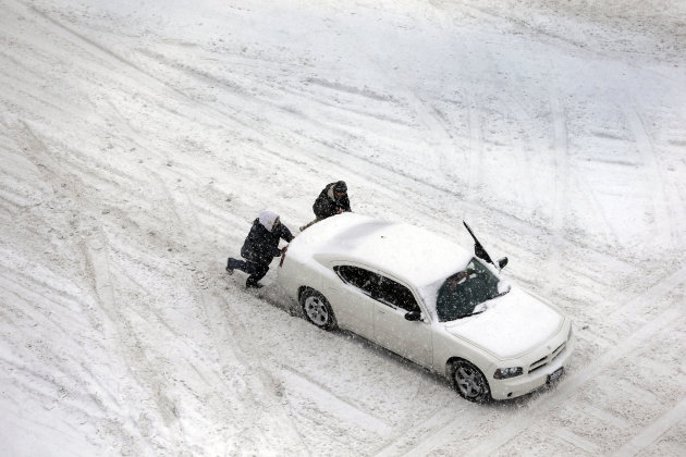 Two men help push a car down a snow-covered street Thursday, Feb. 21, 2013, in St. Louis. Blinding snow bombarded much of the nation's midsection Thursday, causing whiteout conditions, making major ro