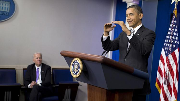 Vice President Joe Biden, left, listens as President Barack Obama gestures as he talks about the fiscal cliff negotiations during a news conference in the briefing room of the White House on Wednesday, Dec. 19, 2012 in Washington.  Obama also announced that Biden will lead an administration-wide effort to curb gun violence in response to the Connecticut school shooting. (AP Photo/ Evan Vucci)