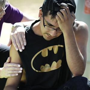 """Isaac Pacheo, who said he was a good friend of theater shooting victim Alex Sullivan, is comforted, Saturday, July 21, 2012, as he visits a memorial near the movie theater in Aurora, Colo.  Twelve people were killed and dozens were injured in the attack early Friday at the packed theater during a showing of the Batman movie, """"Dark Knight Rises.""""   Police have identified the suspected shooter as James Holmes, 24. (AP Photo/Ted S. Warren)"""