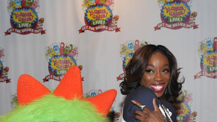 Estelle Swaray, right, poses with Brobee at Yo Gabba Gabba! Live!: Get The Sillies Out! 50+ city tour kick-off performance on Thanksgiving weekend at Nokia Theatre L.A. Live on Friday Nov. 23, 2012 in Los Angeles. (Photo by John Shearer/Invision for GabbaCaDabra, LLC./AP Images)