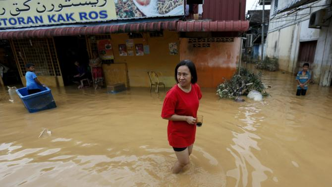 A woman holds her coffee cup as she walks through a flooded street on the outskirt of Kota Bharu in Kelantan