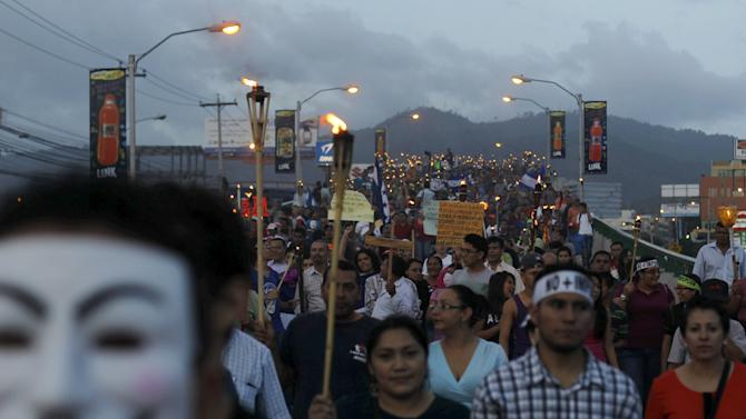 People take part in a march to demand the resignation of Honduras' President Juan Hernandez in Tegucigalpa