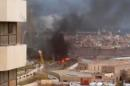 In this image made from video posted by a Libyan blogger, the Cortinthia Hotel is seen under attack in Tripoli, Libya, Tuesday, Jan. 27, 2015. Gunmen stormed the luxury hotel in the Libyan capital of Tripoli on Tuesday, killing several foreigners and guards, officials said. The attack, which included a car bombing, struck the hotel, which sits along the Mediterranean Sea. The blogger, @AliTweel, captured the moments shortly after the blast, when flames rose up from outside the hotel, appearing to be from the aftermath of the car bomb. (AP Photo/ @AliTweel via AP video)