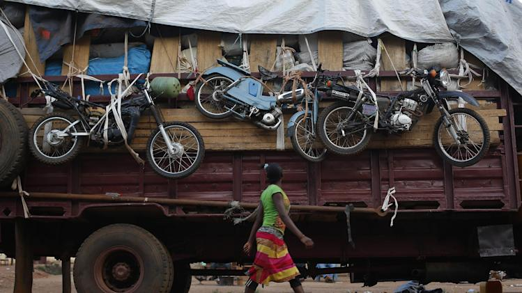 A woman walks past a truck waiting to leave for Chad loaded with goods belonging to Muslim residents of the PK5 district of Bangui, Central African Republic, Wednesday April 9, 2014. The U.S. ambassador to the United Nations on Wednesday urged more support for existing African and French troops in Central African Republic on the eve of a U.N. vote to create a peacekeeping mission. (AP Photo/Jerome Delay)