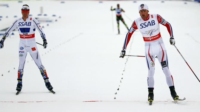 Norway's Northug crosses the finish line ahead of Sweden's Halfvarsson to win the men's cross country free/classic 4 x 10 km relay final at the Nordic World Ski Championships in Falun