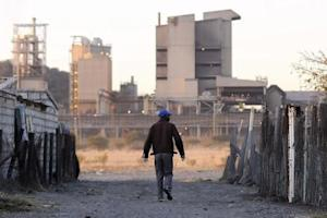 A township resident walks past Lonmin's Marikana platinum mine