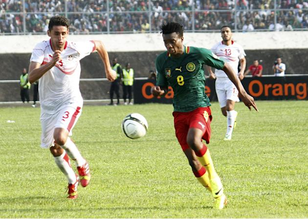 Cameroon's Benjamin Moukandjo, right, is challenged by Tunisia's Hagui Karim in their World Cup qualifying playoff second leg soccer match, in Yaounde, Cameroon, Sunday, Nov. 17, 2013. Cameroon qualif