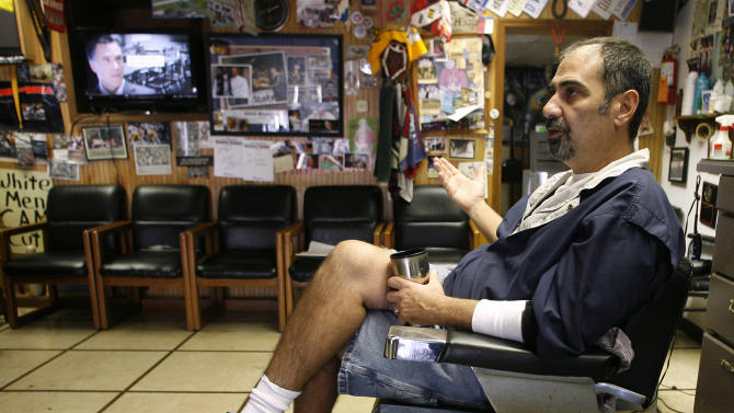 "This photo taken Oct. 26, 2012, shows barber Thomas Checkler, owner of The Old Village Barber in Worthington, Ohio, discussing the impact that the barrage of political ads have on him and his customers during this campaign as an television ad for Republican presidential candidate, former Massachusetts Gov. Mitt Romney is seen at left, in Worthington, Ohio. Humor is also how Checkler deals with election madness in his self-described ""man cave"" in Worthington, an upscale suburb of Columbus. Surrounded by football and hunting memorabilia. (AP Photo/Mike Munden)"