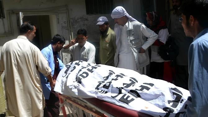 The body of a Hazara shopkeeper is moved after he was killed by unidentified gunmen in Quetta, in an incident that left at least four people killed and eight wounded on May 25, 2015