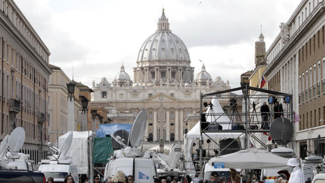Media gather in front of St. Peter's Basilica, at The Vatican, Tuesday, Feb. 12, 2013.  With a few words in Latin, Pope Benedict XVI did what no pope has done in more than half a millennium, stunning the world by announcing his resignation Monday and leaving the already troubled Catholic Church to replace the leader of its 1 billion followers by Easter. (AP Photo/Riccardo De Luca)