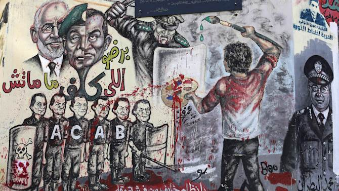 """Boys sit in front of graffiti and Arabic, bottom, that reads, """"regime you're afraid of a paint brush and a pen,"""" in Tahrir Square in Cairo, Monday, Dec. 10, 2012. The Egyptian military on Monday assumed joint responsibility with the police for security and protecting state institutions until the results of a Dec. 15 constitutional referendum are announced. (AP Photo/Hassan Ammar)"""
