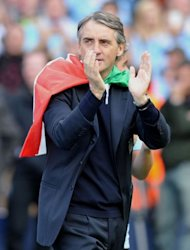 Manchester City's Italian manager Roberto Mancini celebrates on the pitch after their 3-2 victory over Queens Park Rangers in the English Premier League football match between Manchester City and Queens Park Rangers at The Etihad stadium in Manchester