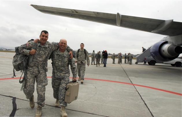 Sgt. Jared Doohen of Georgia, Vt., left, and Staff Sgt. Thomas Stanley of Montgomery, Vt. celebrate their return during a homecoming for Vermont National Guard troops on, Monday, Nov. 22, 2010 in Sout