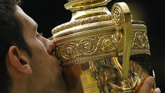 ALTERNATIVE CROP OF WIM336 Serbia's Novak Djokovic kisses the trophy after defeating Spain's Rafael Nadal in the men's singles final at the All England Lawn Tennis Championships at Wimbledon, Sunday, July 3, 2011. (AP Photo/Kirsty Wigglesworth)
