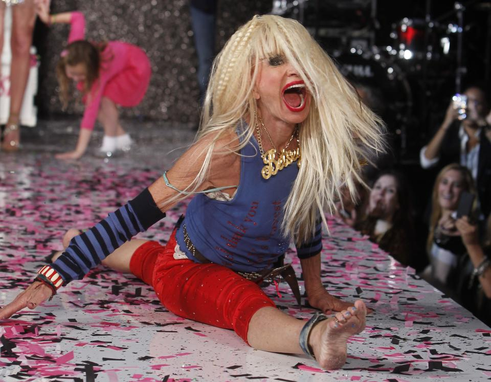 Designer Betsey Johnson goes into a split after doing a cartwheel on the runway after the Betsey Johnson Spring 2013 collection show during Fashion Week, Tuesday, Sept. 11, 2012, in New York. (AP Photo/Jason DeCrow)